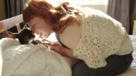 Redhead woman sitting in bed petting her small dog video