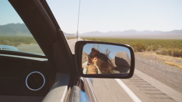 Reflection Of Couple Driving In Convertible Car Shot On R3D video