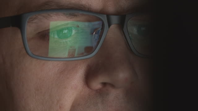 Reflection of scrolling sites in an eyeglasses of young adult man who works on a computer video