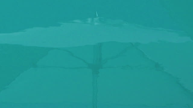 Reflections of big umbrella on a pool water background video