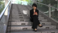 Relax For Asian Businesswoman Texting With Smartphone Sitting On Stairs video