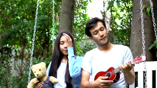 Relaxed asian young couple play guitar on white swing at home video