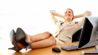 Relaxed businesswoman putting her feet up smiling at camera video