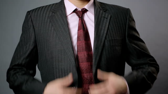 Relaxed office worker taking black jacket off after hard working day, closeup video