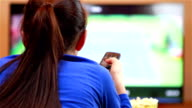 Relaxed teenage girl with remote control watching smart TV video