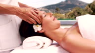 Relaxed woman getting a head massage poolside video