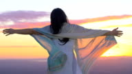 relaxed woman opens her arms to the sun: sunset, contemplation, meditation, yoga video