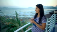 Relaxed woman using a smart phone in a bar or hotel terrace on holidays. video