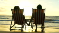 Relaxing Couple on Tropical Resort Luxury Vacation. Beach Chairs in the Sunset. video