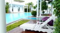 Relaxing pool chair beside of swimming pool in hotel. video