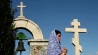 Religious woman praying to God. Monastery, stone crosses, solitude, spirituality video