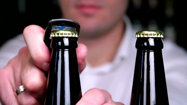 Removing the caps from bottles of beer closeup video