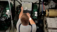 Repairer performs diagnostics of the yacht engine video