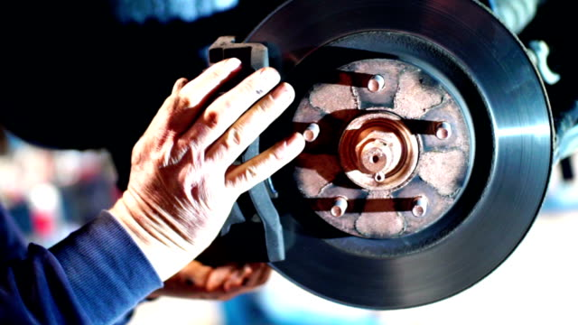 Replacing brake pads on a car at a workshop. video