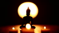 replica of Buddha statue and moving candle flames video