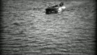 1934: Rescue lifesaving boat picks up drowning man in deep dark waters. video