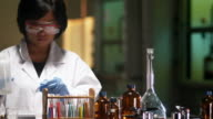 Researcher in lab filling test tube Dolly right to left video