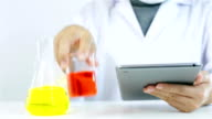 Researcher working with chemicals note to tablet video