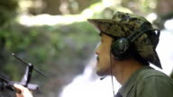 Researchers listen to the radio signal from radio telemetry,tracking to find an wildlife in tropical rainforest video