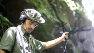 Researchers listen to the radio signal from radio telemetry,tracking to find an wildlife in tropical rainfores video