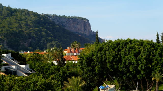 resort area, tall cliff, green trees and palms, roofs of houses, sunny day, calm weather video