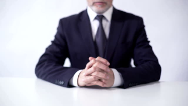 Respectable businessman sitting at office table, ready to discuss cooperation video