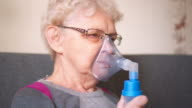 Respiratory oxygen nasal catheter to senior woman video