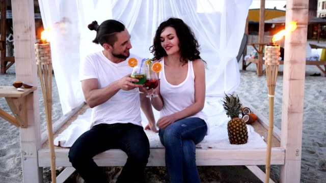 Rest on beach, loving couple having cocktail in hands, men and women mixed drink, friends with cocktail on tropics, young people drinking video