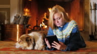 Rest together with your favorite dog. A young woman reading something on the plate against the background of the fireplace video