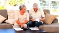 Retired couple calculating their domestics bills video