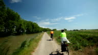 Retired couple cycling beside river video