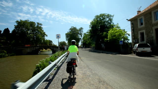 Retired couple cycling on road beside river video