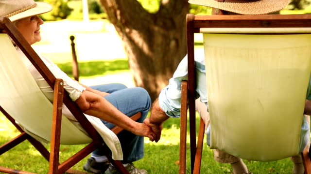 Retired couple sitting in deck chairs holding hands video