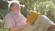 Retired elderly man relaxing outdoors reading a book enjoying retirement video