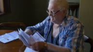 Retired farmer old man with financial difficulty looking at bills video