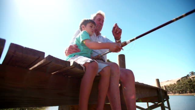Retired grandfather teaching his grandson to fish video