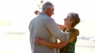 Retired old couple embracing each other while holding flower video