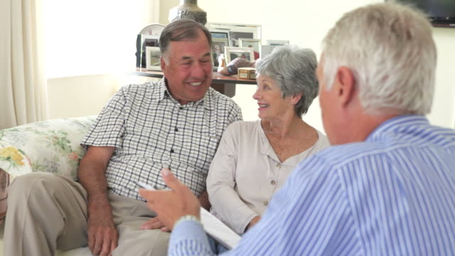Retired Senior Couple Sitting On Sofa Talking To Financial Advisor video