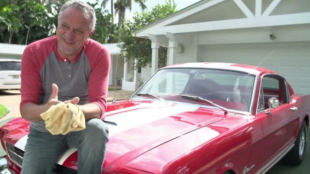 Retired Senior Man Sitting On Hood Of Restored Classic Car video
