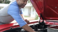 Retired Senior Man Working On Restored Car In Slow Motion video