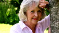 Retired woman leaning against tree smiling at camera video