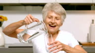 Retired woman pouring glass of water video