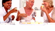 Retired women having cupcakes and tea together video