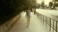 Retro looking image of catwalking women in daytime alley in urban setting video
