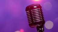 Retro microphone against blurry purple stage lighting with glitter confetti video