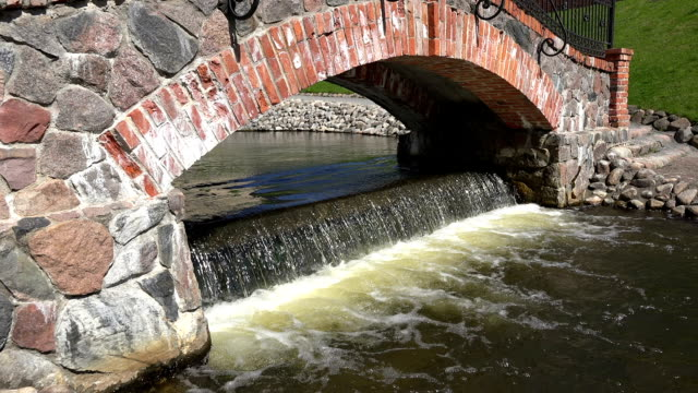 Retro red brick and stone arch and waterfall water flowing video