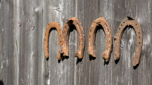 Retro rusty horse shoe hand unhanging old wooden rural house wall. Closeup. video