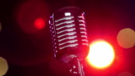 Retro shiny microphone rotating against blurry flashing lights. Close-up video