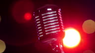 Retro shiny microphone slow rotating against blurry flashing lights video