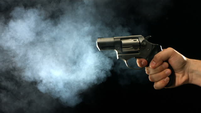 Revolver shooting and smoking, slow motion video